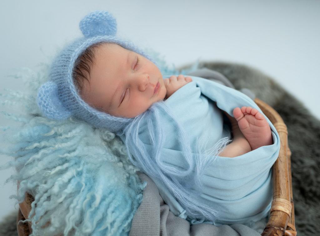 nouveau-né emmailloté de bleu bonnet d'ourson endormi sur fluffy bleu photographe naissance nouveau-né Houilles Yvelines la Défense