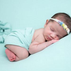 nouveau-né bébé fille endormie sur posing bag vert menthe sur le ventre photographe naissance nouveau-né bébé Houilles Yvelines la Défense
