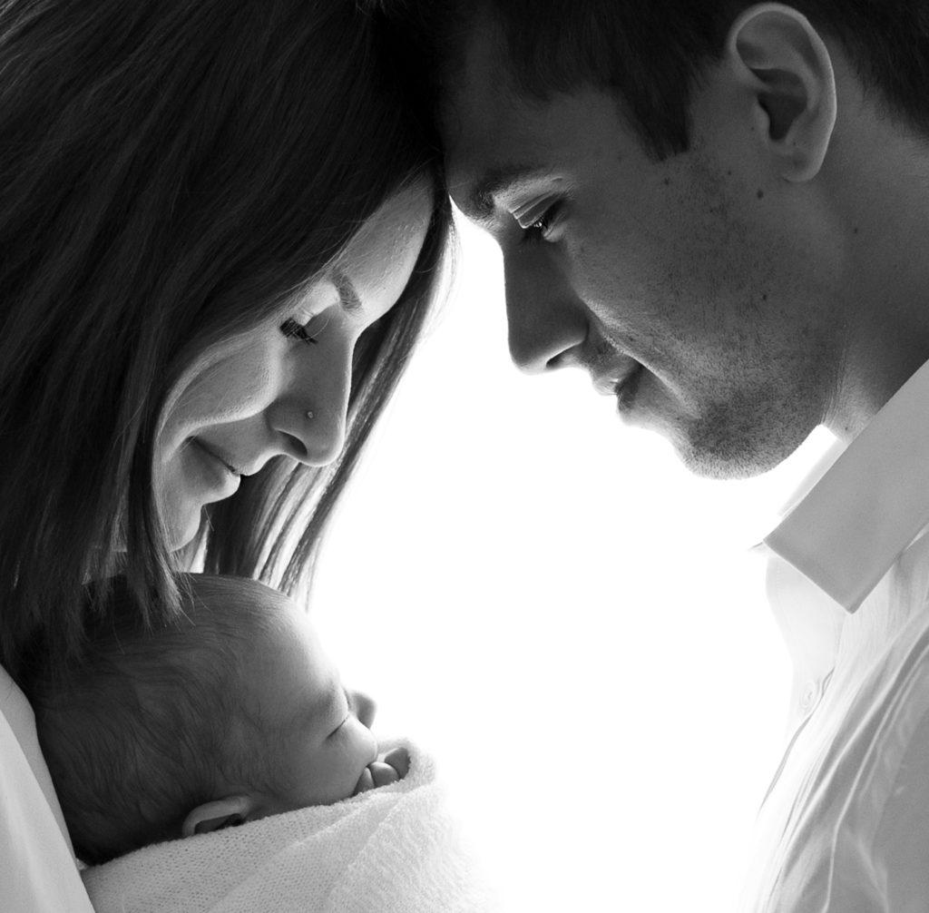 Couple de jeunes parents en contrejour regardant leur nouveau-né profil noir et blanc photographe naissance bébé Houilles Yvelines la Défense